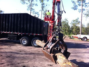 Tree removal crew member uses equipment to move log into truck - step 1